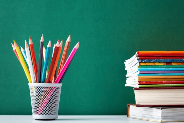 Close-up of colorful pencils with textbooks Free Photo
