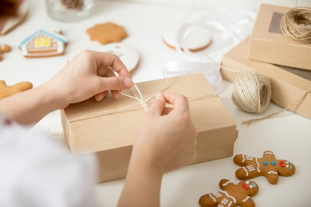 Close up of confectioner hands wrapping a cardboard box Free Photo