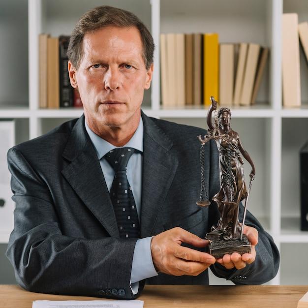 Крупный план уверенный зрелый мужчина-юрист, показывающий статую правосудия Бесплатные Фотографии