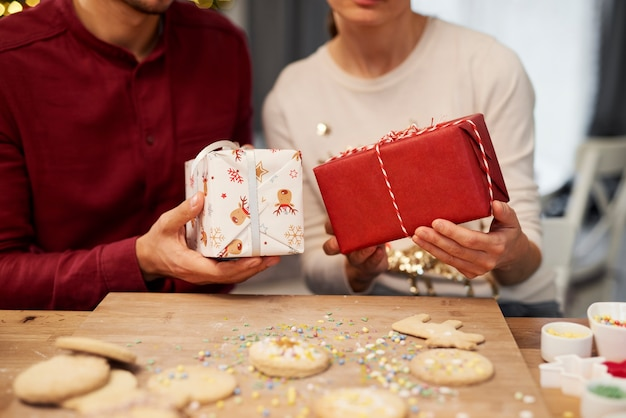 クッキーとクリスマスプレゼントを保持しているカップルのクローズアップ 無料写真