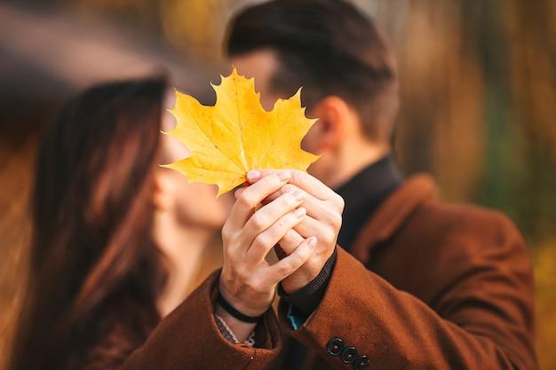 Крупным планом пара с желтым кленовым листом, целующаяся в осеннем парке Premium Фотографии
