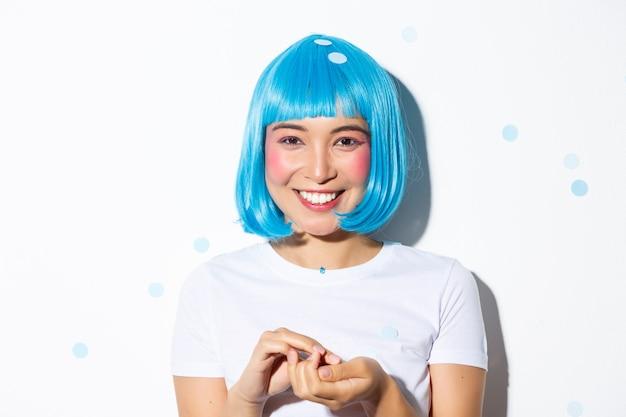 할로윈을 축 하 하 고 색종이를 던지고 웃 고, 서있는 파란색가 발에 귀여운 아시아 여자의 클로즈업. 무료 사진