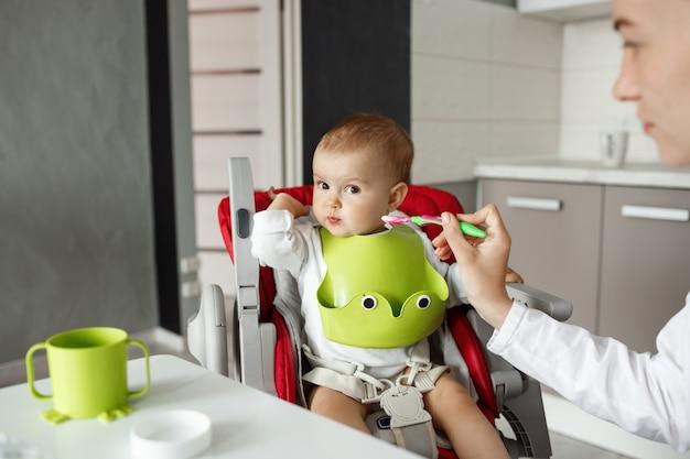 Закройте милый маленький сын, сидящий на кухне в детском кресле и поворачивающий голову, отказываясь есть детское питание. мать пытается кормить его ложкой. Бесплатные Фотографии