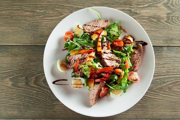 Крупным планом деликатесный овощной салат, включая ломтики телятины, перепелиные яйца, помидоры черри. вкусный к ресторанной трапезе с легким красным или белым вином или шампанским. Бесплатные Фотографии