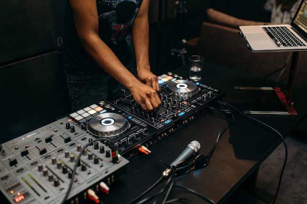 파티 축제에 턴테이블에서 음악을 연주하는 Dj의 손을 가까이 프리미엄 사진