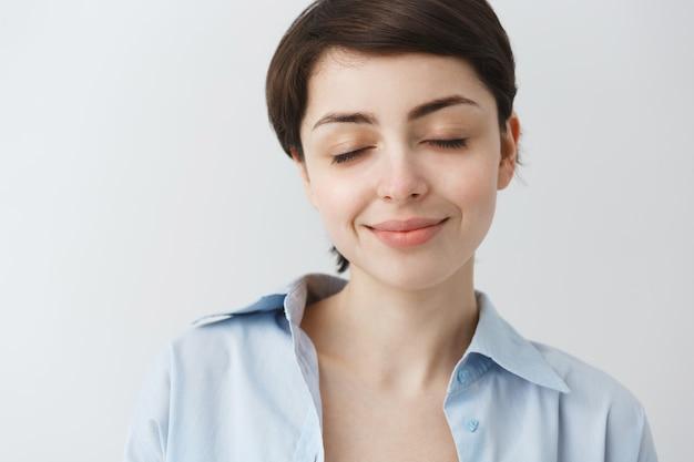 Крупный план мечтательной привлекательной девушки с закрытыми глазами и улыбкой, мечтающей о чем-то приятном Бесплатные Фотографии