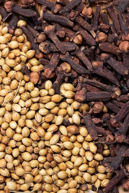 乾燥コリアンダーシードとクローブ、食品の香りと自然医学、インドのスパイスの成分の乾燥スパイシーハーブのクローズアップ Premium写真