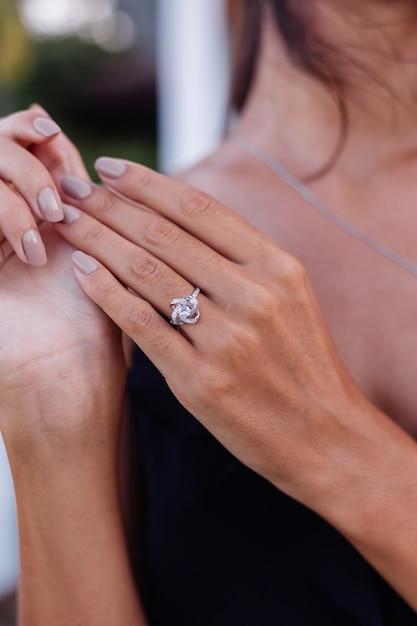 女性の指のエレガントなダイヤモンドリングのクローズアップ。黒のドレスを着ている女性。愛と結婚式のコンセプト。柔らかな自然光とセレクティブフォーカス。 無料写真