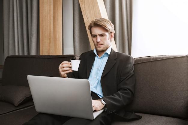 Закройте элегантный небритый мужчина пьет кофе, глядя в ноутбук монитор с серьезным и неудовлетворенным выражением, работая из дома. Бесплатные Фотографии