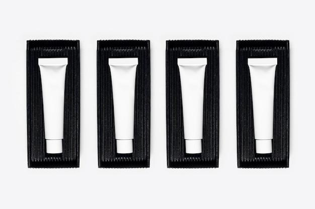흰색 표면에 블랙 박스에 포장 빈 화장품 튜브 병의 근접 프리미엄 사진