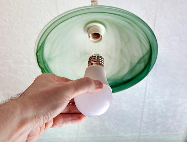 인간의 손에있는 에너지 절약형 Led 전구의 클로즈업, 녹색 바닥 유리로 만든 천장 조명기구의 램프 교체. 프리미엄 사진