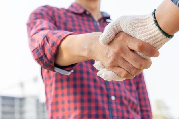 Закройте вверх рукопожатия инженера и работника с запачканной строительной площадкой, успешной концепцией Premium Фотографии