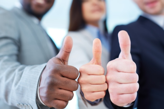 Close-up of executives showing thumbs up Free Photo