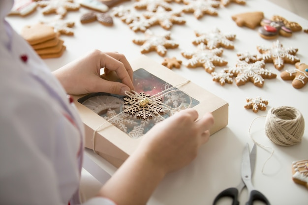 Close up of female confectioner hands wrapping a box Free Photo
