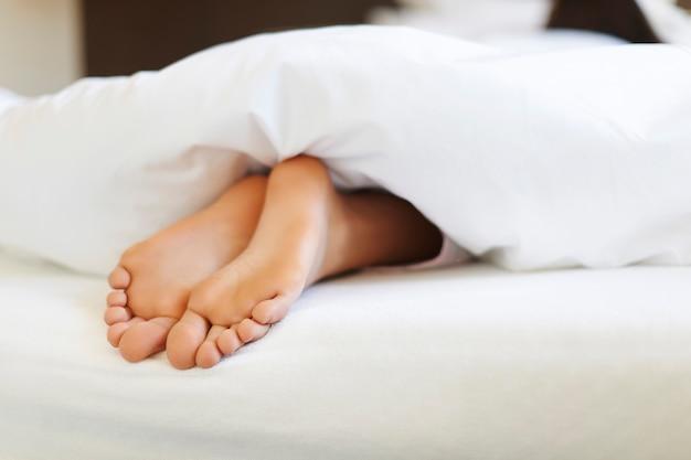 Крупным планом женские ноги в постели Бесплатные Фотографии
