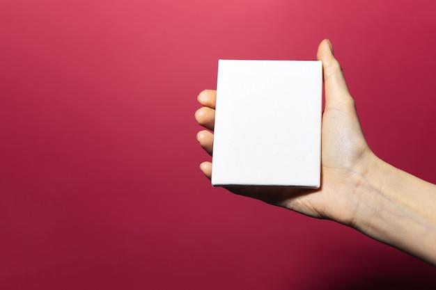 핑크 산호 색상의 표면에 모형과 함께 백서를 들고 여성 손 클로즈업 프리미엄 사진