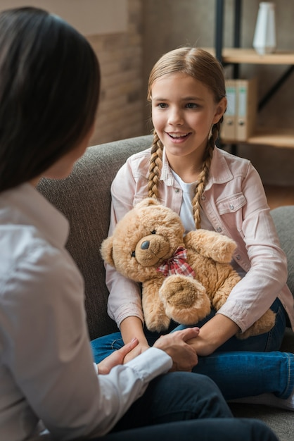 Close-up of female psychologist holding hands of her patient with teddybear Free Photo