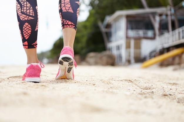ピンクのスニーカーとレギンスを着て歩いたり、ぼやけたバンガローに対して屋外で運動しながらビーチの砂の上を実行している女性ランナーのクローズアップ。後ろから見たところ。 無料写真