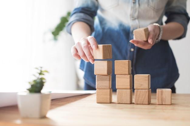 Конец-вверх руки женщины штабелируя деревянный блок на таблице на офисе Premium Фотографии