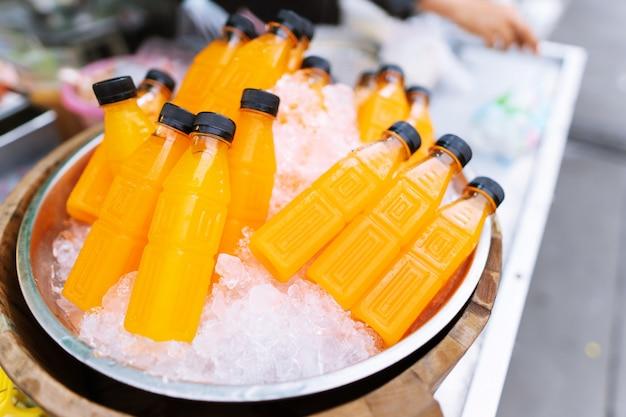 Крупным планом свежего апельсинового сока в пластиковой бутылке Premium Фотографии