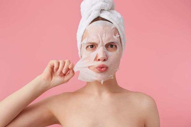 얼굴에서 패브릭 마스크를 제거하려고 샤워 후 그녀의 머리에 수건으로 인상을 찌푸린 젊은 여성의 닫습니다. 무료 사진