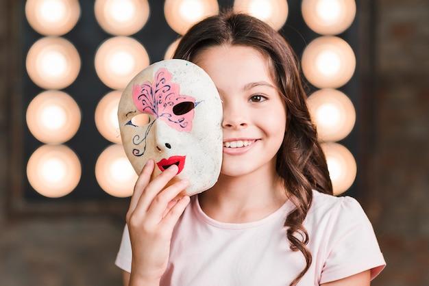 彼女の顔の前にベネチアのマスクを保持している女の子のクローズアップ Premium写真