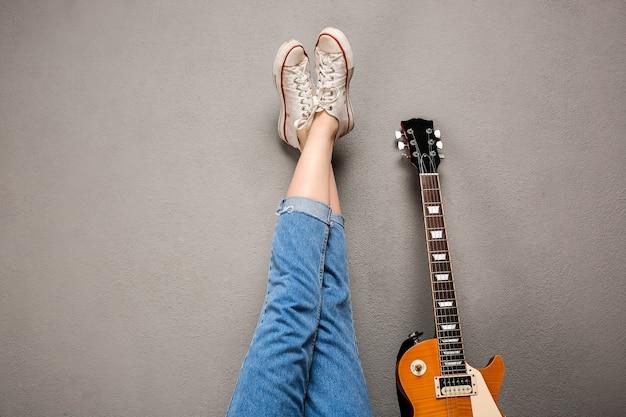 少女の足と灰色の背景上のギターのクローズアップ。 無料写真