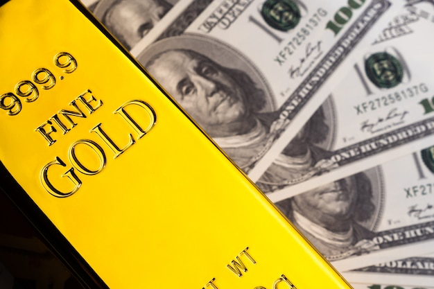 Закройте вверх золотого слитка и банкнот. финансовая концепция Premium Фотографии