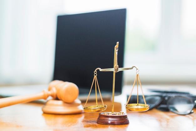 Крупный план шкалы золотого правосудия на деревянном столе в зале суда Premium Фотографии
