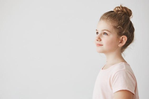 パン髪型のブロンドの髪を持つかっこいい女の子のクローズアップ。4分の3に立って、笑顔でよそ見をしています。 無料写真