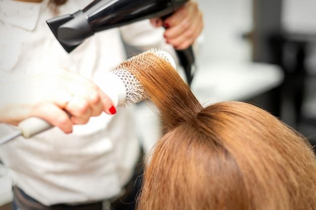 미용실에서 헤어 드라이어와 둥근 브러시로 긴 빨간 머리를 건조하는 미용사의 닫습니다 프리미엄 사진