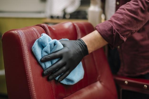Крупный план парикмахера, чистящего кресло Premium Фотографии