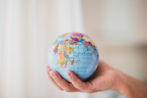 Close-up of hand holding small globe Free Photo