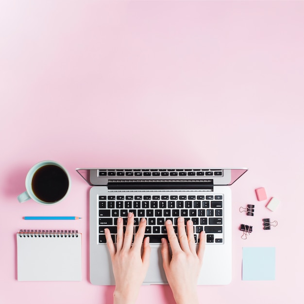 Close-up of hand typing on laptop with stationeries and coffee cup on pink backdrop Free Photo