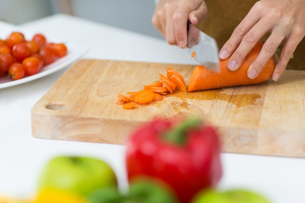 Close-up of hands chopping carrot on cutting board Free Photo