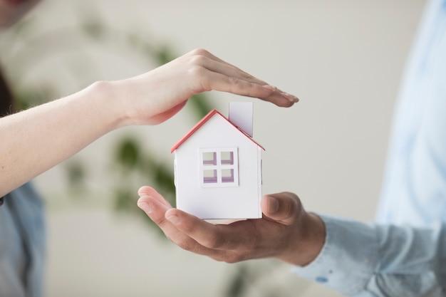 Макро руки, защищая модель небольшого дома Premium Фотографии