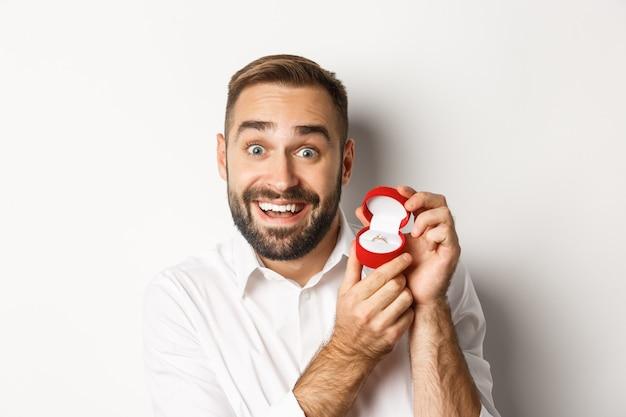 提案をし、希望を持って結婚指輪を見せ、彼と結婚するように頼むハンサムな男のクローズアップ 無料写真