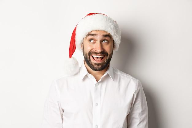 クリスマスと新年を祝い、左上隅を見て、何かをイメージして、サンタの帽子をかぶった幸せなひげを生やした男のクローズアップ。白色の背景。 無料写真