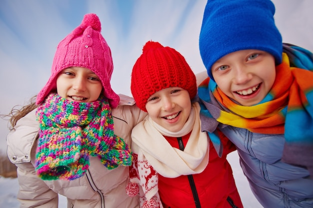 Close-up of happy kids with wool hats and scarves Free Photo