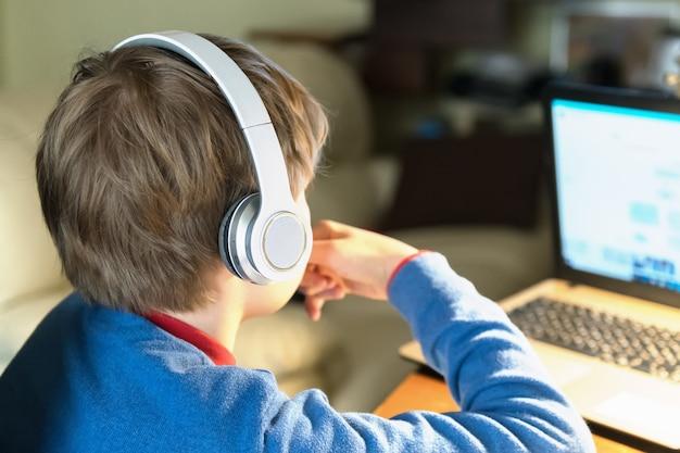 ノートブックを机の上に座っているヘッドフォンで金髪の子供男の子の頭のクローズアップ。ホームスクーリングと自宅オンラインからの教育 Premium写真