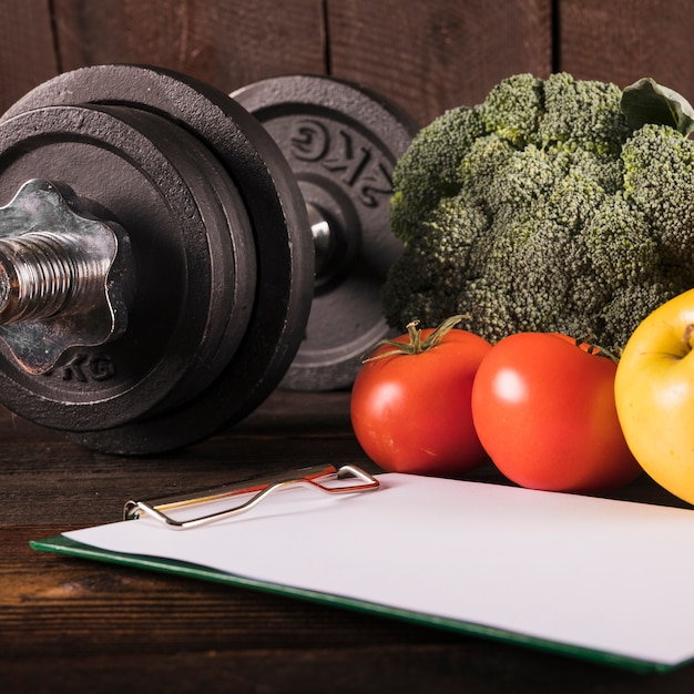 Close up of healthy raw food and dumbbell on wooden desk 23 2147882034