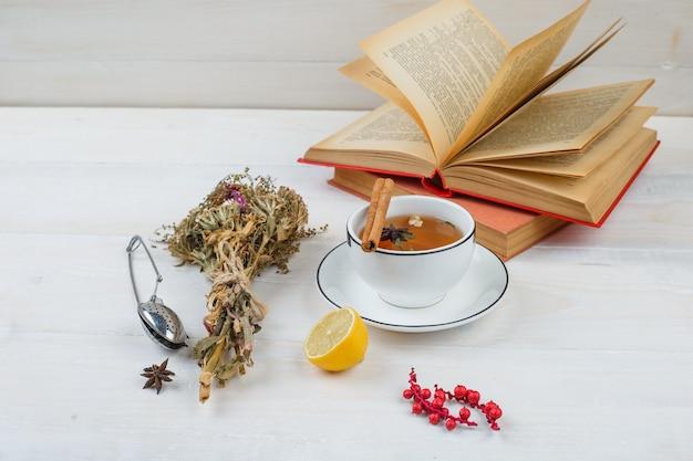 Крупный план травяного чая и цветов с лимоном, ситечком для чая и специями Бесплатные Фотографии