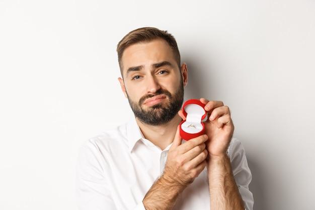Крупный план обнадеживающего мужчины, который умоляет выйти за него замуж, выглядит грустным и показывает обручальное кольцо, делая предложение Бесплатные Фотографии
