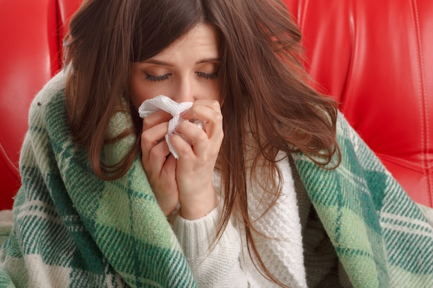 Close-up of ill teenager with a tissue next to her nose Free Photo
