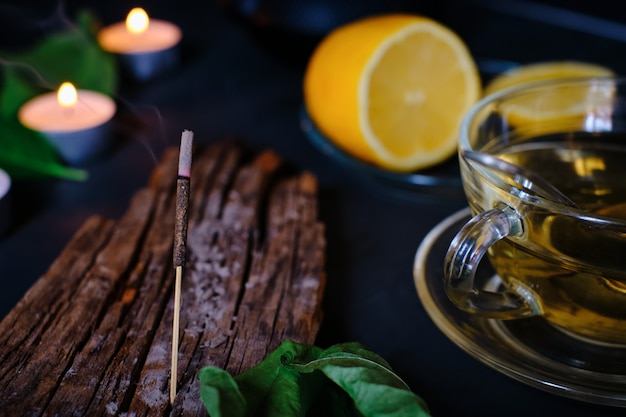 Крупный план ароматическая палочка, свечи, лимон и чашка зеленого чая Premium Фотографии