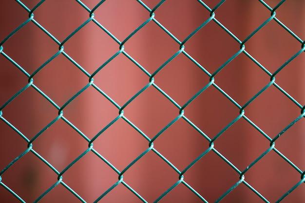 Конец-вверх изолированной покрашенной простой геометрической сцены загородки звена цепи провода металла черного листового железа темной красной. концепция ограждения, защиты и ограждения. Premium Фотографии