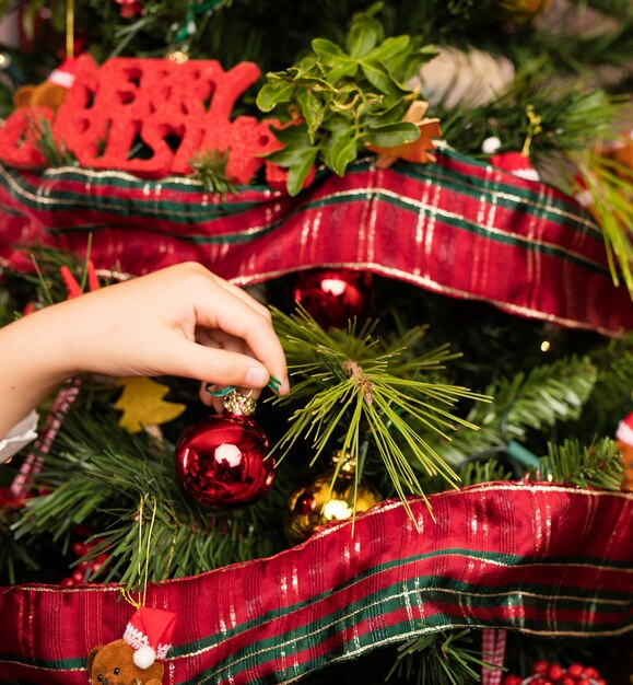 Kids Decorating Christmas Tree: Close-up Of Kids Decorating A Tree On Christmas Photo