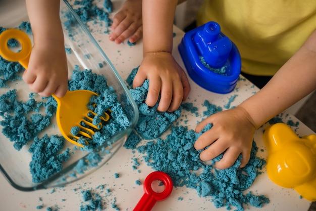 Конец-вверх кинетического песка и набора ящика с песком. руки ребенка играют с песком. Premium Фотографии