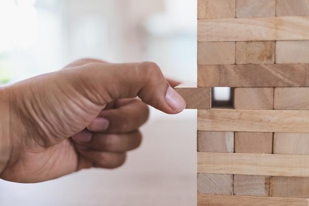 男の左手のクローズアップは、木製の塔(ジェンガ)から木の棒を取り出します。横からの眺め Premium写真