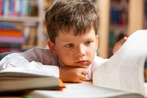 Close-up of little boy reading a book Free Photo